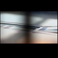 Image: still from video showing edges of printed paper photographs on a floor, with shadows cast upon them