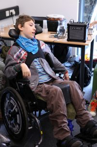 Young boy in wheelchair with music tech