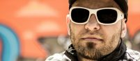 Close up on the face of rapper Billy Saga wearing white sunglasses and with a short beard