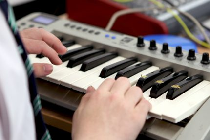 Keyboard in close up, with hands playing