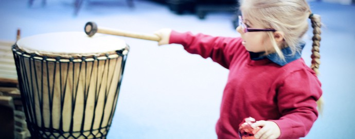 Image: Little girl with focussed expression playing large drum