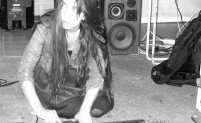 Black and white photo of Melanie Clifford playing a guitar on the floor.