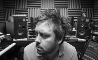 Black and white photo of Kris Halpin in a recording studio looking pensive