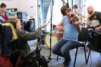 A young disabled musician conducts a jam session with a range of musicians and instruments