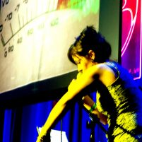 Colourful photo of Caro performing on stage, with VU meter projected in background.