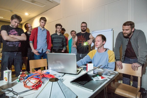 Group photo of all hackers and musicians looking at laptop