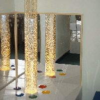 Image: Corner of room with mirrored walls and tall clear plastic tube containing bubbles lit up from below.