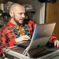 Daryl wears a colourful top and looks at a laptop, surrounded by music technology