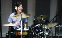 Image: Tom Newnham playing drums and laughing
