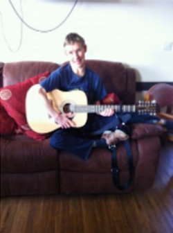 Image: Joe Rushbrook playing acoustic guitar and smiling