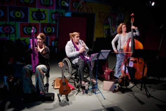Three musicians playing classical instruments onstage in the spotlight