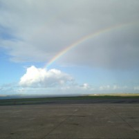 A rainbow disappearing into a cloud, over the runway at Kirkwall Airport, Orkney