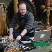 Image of Charles Matthews playing with some tech attached to his laptop.