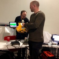 Gawain Hewitt demonstrating the Kellycaster in the foreground with Charles Matthews on laptop in the background