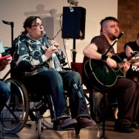 Disabled musicians on stage playing together, informally