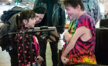 A young girl smiles at a Disabled musician as he shows her something on an ipad