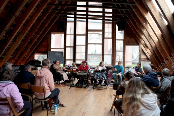 Electric Storm Ensemble gathered at the front of a large room made of wood & windows