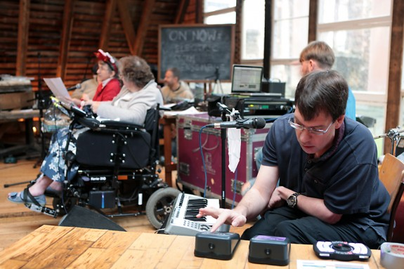 A man plays colourful switches with musicians in the background with lots of tech