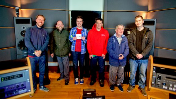 Amplify musicians standing in mastering studio holding a copy of their CD