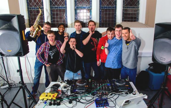 Full group of 7 musicians behind the decks with Luke and Ben from Drake Music, celebrating and giving thumbs up