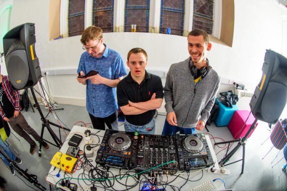 Picture with cool fisheye lens effect showing 3 Amplify musicians posing behind the decks