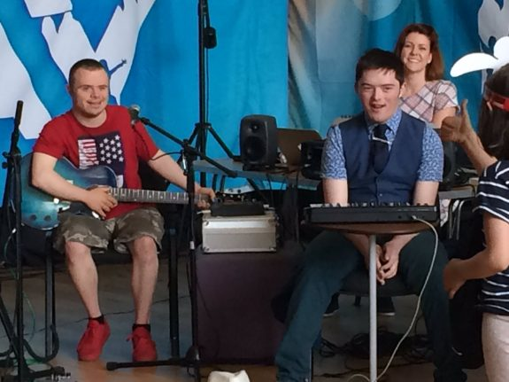 Young musicians on stage at Fast Forward Festival, smiling with instruments