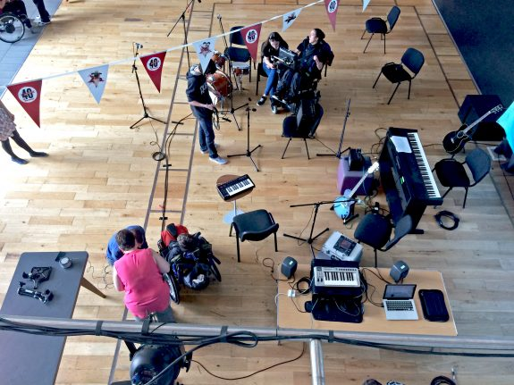A view from above the stage looking down at musicians setting up keyboards, iPads and amps