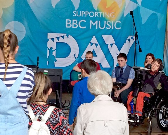 A view from behind the crowd watching a groups of young musicians perform in front of a big BBC Music Day banner