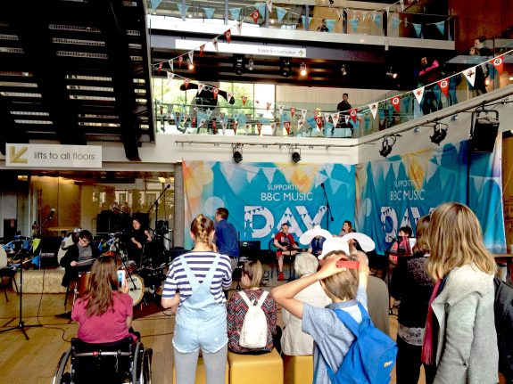 wide shot of Colston Hall foyer showing audence and musicians