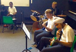 4 young musicians playing together, 2 bass guitars, drums, electric drum pads