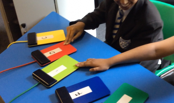 Two school children playing a selection of coloured switches laid out on a table.