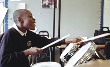 Young pupil smiling playing drum kit