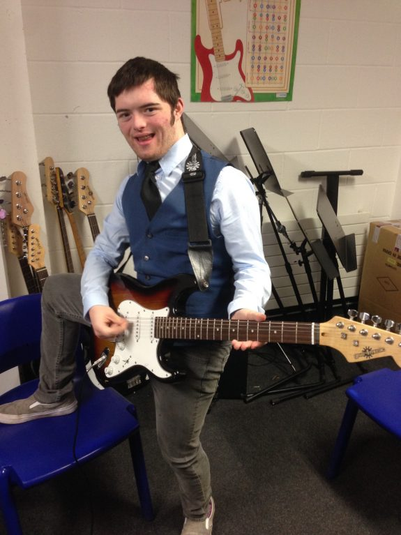 Young musician smiles and plays electric guitar