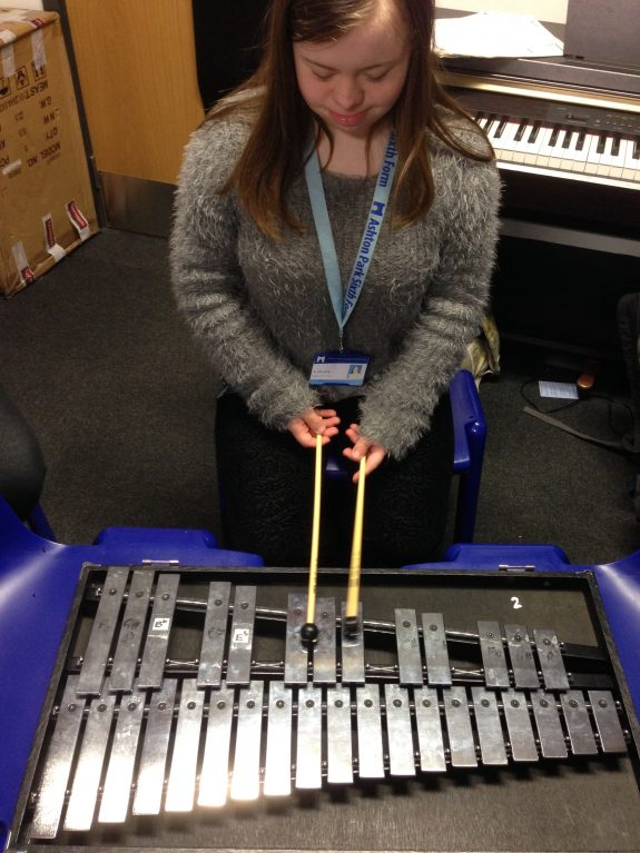 Young female musician kneels and plays glockenspiel