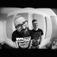 Black and white photo with distorted perspective of two male musicians
