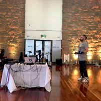 Colour photograph of Kris Halpin performing in a large room with computers, wires & mi mu gloves