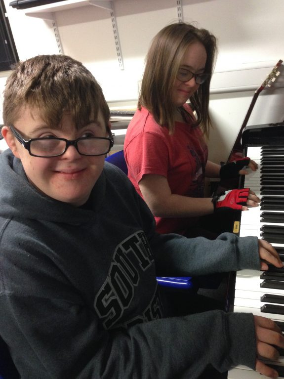 two young people play electric keyboard