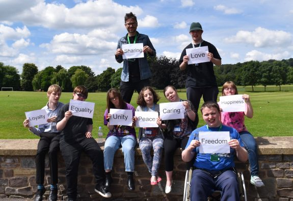 A group of young people outdoors in casual clothes holding cardss with words on