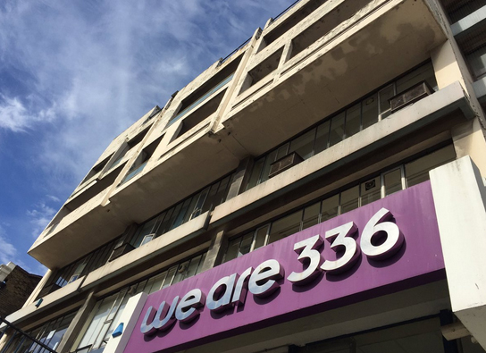 Colour photo of the we are 336 building shot at an angle with blue sky