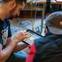 a music leader plays iPad with a young participant