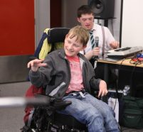Two young disabled musicians smiling and playing music