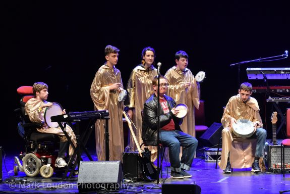6 band members onstage in long gold robes playing different instruments