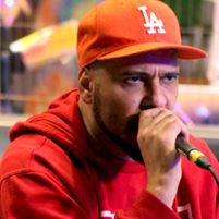 Brazilian rapper Billy Saga performing wearing a red baseball cap and red hoodie