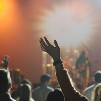 Image of a concert from the viewpoint of the crowd, with waving hands, bright lights & musicians blurred in the distance