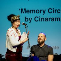 Musician Cina Aissa introduces her sound art work onstage with Daryl
