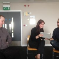 Two people look at a shared ipad