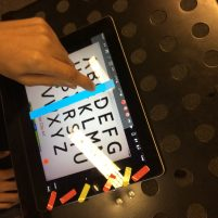 ipad with alphabet displayed and a person pressing the screen