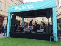 A blue marquee houses a small stage where the performers are gathered with their instruments