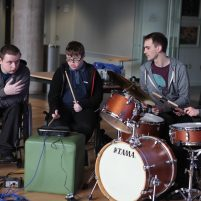 Three young men sit with their instruments including drums and electronic devices