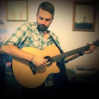 Michael Dollan plays acoustic guitar